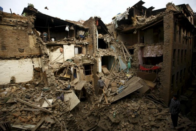People search for family members trapped inside collapsed houses a day after an earthquake in Bhaktapur, Nepal April 26, 2015. A shallow earthquake measuring 7.9 magnitude struck west of the ancient Nepali capital of Kathmandu on Saturday, killing more than 100 people, injuring hundreds and leaving a pall over the valley, doctors and witnesses said. (REUTERS/Navesh Chitrakar)