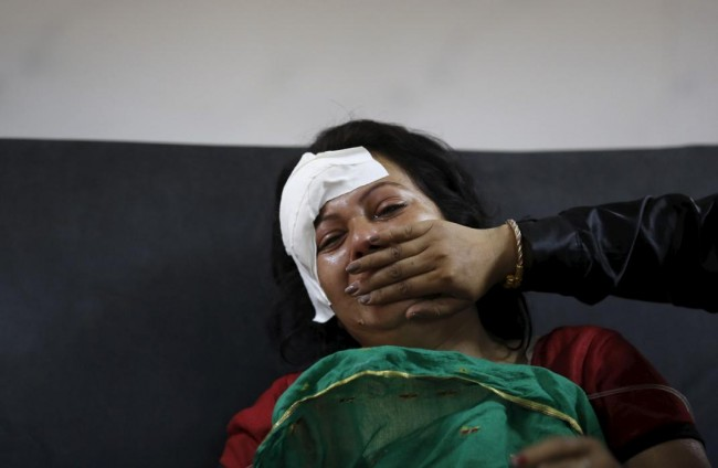 An injured woman cries after hearing news of a family member who died during an earthquake at a trauma center in Kathmandu, Nepal April 26, 2015. Rescuers dug with their bare hands and bodies piled up in Nepal on Sunday after the earthquake devastated the heavily crowded Kathmandu Valley, killing more than 2,200 people, and triggered a deadly avalanche on Mount Everest. (REUTERS/Adnan Abidi)