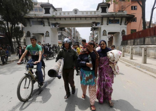 A family carry their belongings as they rush for safety during a strong aftershock after an earthquake, in Kathmandu, Nepal April 26, 2015. Rescuers dug with their bare hands and bodies piled up in Nepal on Sunday after the earthquake devastated the heavily crowded Kathmandu Valley, killing more than 2,200 people, and triggered a deadly avalanche on Mount Everest. (REUTERS/Adnan Abidi)