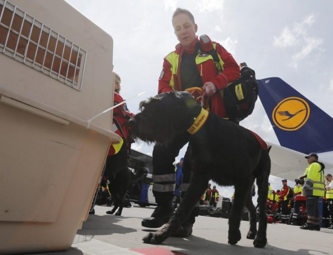 Sniffer dog handler Susanna Martin-Schmitt of Germany's NGO organistation International Search and Rescue (ISAR- Germany) prepares her dog 'Porthos' to board their flight to Nepal from Frankfurt airport April 26, 2015. Some seven rescue dogs and 51 doctors, medics and logistical experts are flying to Nepal on Sunday, a day after a 7.9 magnitude earthquake devastated the heavily crowded Kathmandu Valley, killing more than 2,200 people, and triggered a deadly avalanche on Mount Everest. (REUTERS/Wolfgang Rattay)