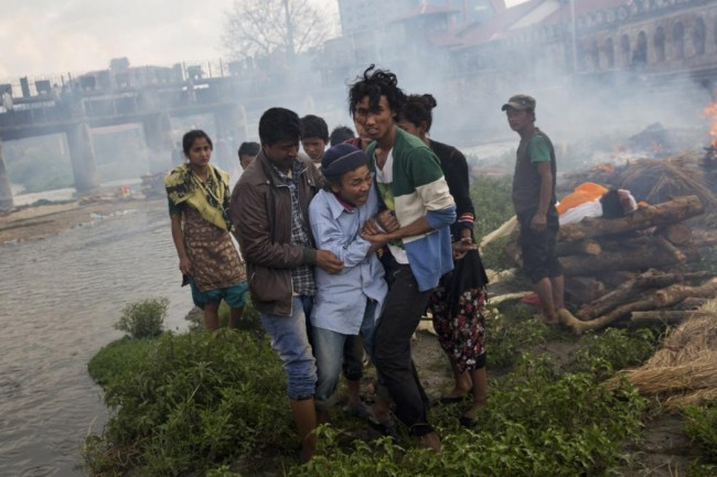 A Hindu man breaks down during a funeral of Saturday's earthquake victims on the Pashupatinath bank of Bagmati river, in Kathmandu, Nepal, Sunday, April 26, 2015.  The earthquake centered outside Kathmandu, the capital, was the worst to hit the South Asian nation in over 80 years. It destroyed swaths of the oldest neighborhoods of Kathmandu, and was strong enough to be felt all across parts of India, Bangladesh, China's region of Tibet and Pakistan.(AP Photo/Bernat Armangue)