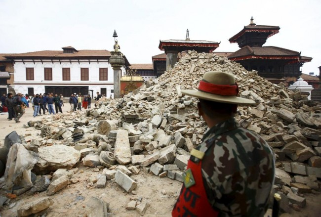 A Nepalese army personnel stands in front of a collapsed temple a day after an earthquake in Bhaktapur, Nepal April 26, 2015. Rescuers dug with their bare hands and bodies piled up in Nepal on Sunday after the earthquake devastated the heavily crowded Kathmandu valley, killing at least 1,900, and triggered a deadly avalanche on Mount Everest.  REUTERS/Navesh Chitrakar