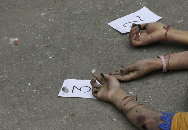 Identification numbers are seen next to dead bodies after an earthquake struck, outside a hospital in Kathmandu, Nepal April 26, 2015. Rescuers dug with their bare hands and bodies piled up in Nepal on Sunday after the earthquake devastated the heavily crowded Kathmandu Valley, killing more than 2,200 people, and triggered a deadly avalanche on Mount Everest. (REUTERS/Adnan Abidi)