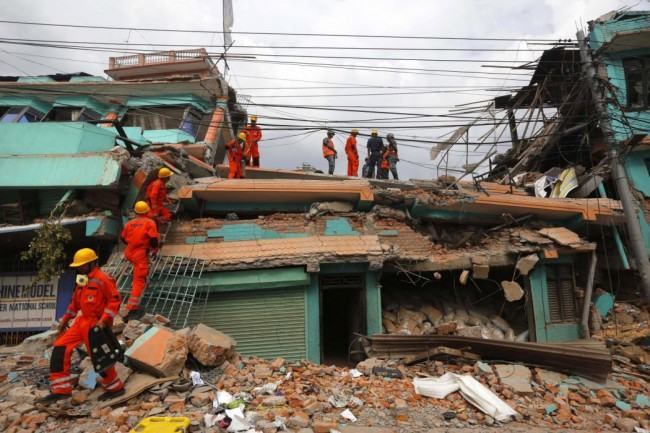 India's National Disaster Response Force personnel look for survivors in a building, in Kathmandu, Nepal, Sunday, April 26, 2015. Sleeping in the streets and shell-shocked, Nepalese cremated the dead and dug through rubble for the missing Sunday, a day after a massive Himalayan earthquake devastated the region and destroyed homes and infrastructure. (AP Photo/Manish Swarup)