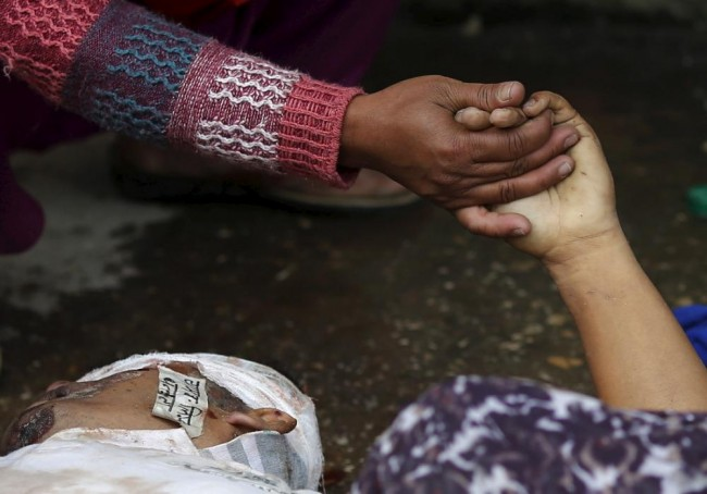 A woman holds the hand of a deceased relative who died during an earthquake outside a hospital in Kathmandu, Nepal April 26, 2015. Rescuers dug with their bare hands and bodies piled up in Nepal on Sunday after the earthquake devastated the heavily crowded Kathmandu Valley, killing more than 2,200 people, and triggered a deadly avalanche on Mount Everest. (REUTERS/Adnan Abidi)