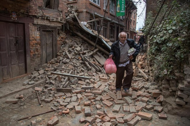 A man runs down a street covered in debris after buildings collapsed on April 26, 2015 in Bhaktapur, Nepal. (Omar Havana/Getty Images)