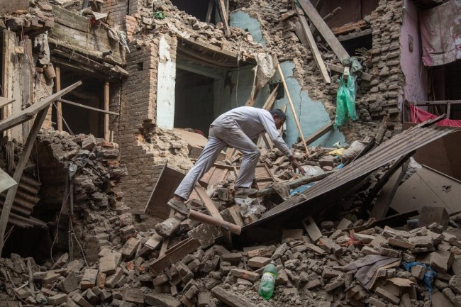 A man climbs on top of debris after buildings collapsed on April 26, 2015 in Bhaktapur, Nepal. (Omar Havana/Getty Images)