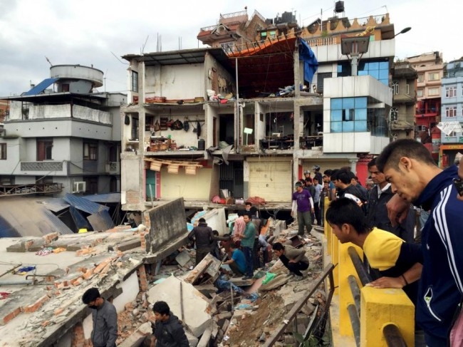 People survey a site damaged by an earthquake, in Kathmandu, Nepal, April 25, 2015. The shallow earthquake measuring 7.9 magnitude struck west of the ancient Nepali capital of Kathmandu on Saturday, killing more than 100 people, injuring hundreds and leaving a pall over the valley, doctors and witnesses said.  (REUTERS/Navesh Chitrakar)