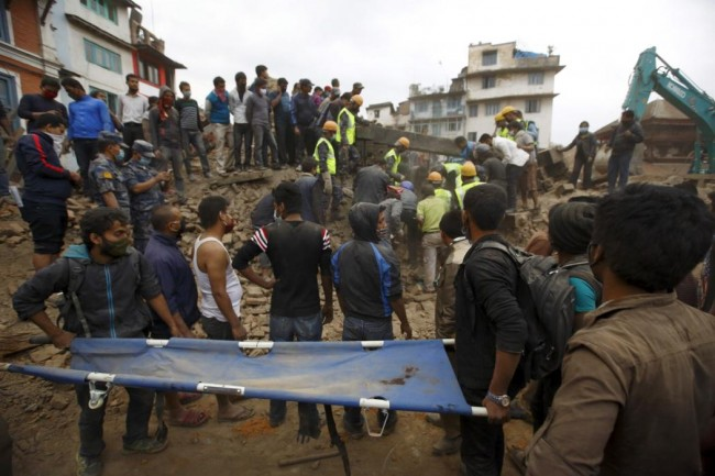 Rescue workers search for bodies as a stretcher is kept ready after an earthquake hit, in Kathmandu, Nepal April 25, 2015. The powerful earthquake struck Nepal and sent tremors through northern India on Saturday, killing hundreds of people, toppling an historic 19th-century tower in the capital Kathmandu and touching off a deadly avalanche on Mount Everest. (REUTERS/Navesh Chitrakar)