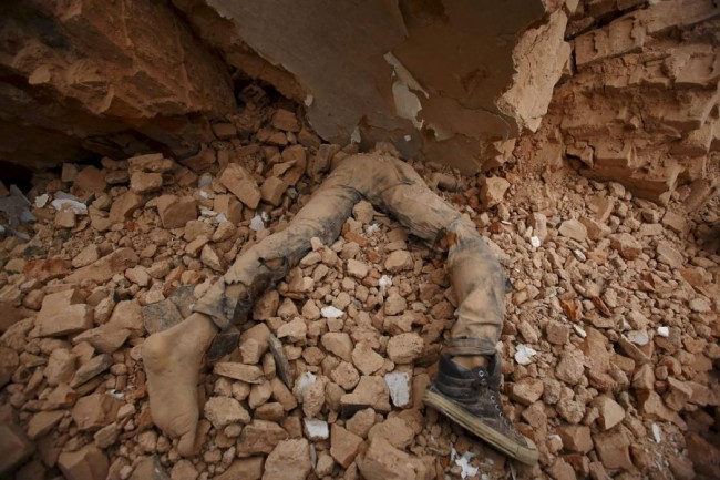 A body of a victim lies trapped in the debris after an earthquake hit, in Kathmandu, Nepal April 25, 2015. The shallow earthquake measuring 7.9 magnitude struck west of the ancient Nepali capital of Kathmandu on Saturday, killing more than 100 people, injuring hundreds and leaving a pall over the valley, doctors and witnesses said. (REUTERS/Navesh Chitrakar)