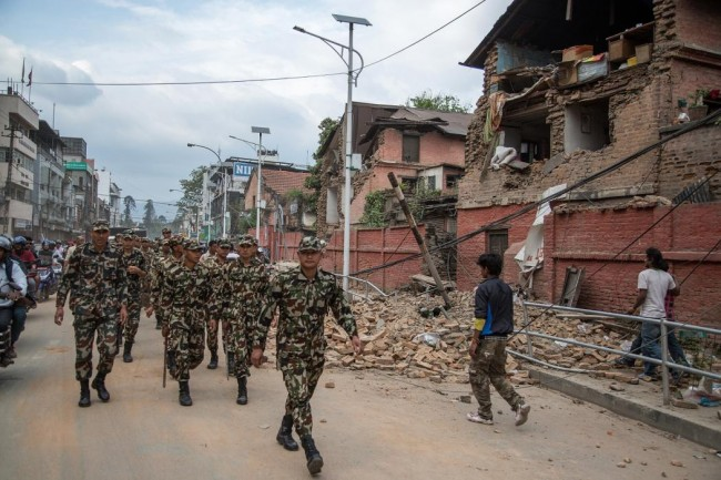 An army patrol walks in the city center looking at the damage following an earthquake on April 25, 2015 in Kathmandu, Nepal. (Photo by Omar Havana/Getty Images)