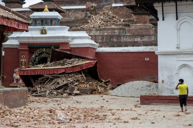 A young man speaks on the phone in front of a collapsed temple in the city center following an earthquake on April 25, 2015 in Kathmandu, Nepal. (Photo by Omar Havana/Getty Images)