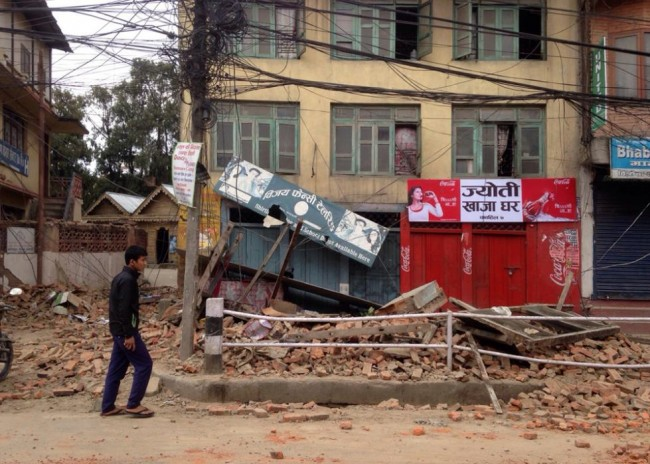 An  man walks past damage caused by an earthquake in Kathmandu, Nepal, Saturday, April 25, 2015. A strong magnitude-7.9 earthquake shook Nepal's capital and the densely populated Kathmandu Valley before noon Saturday, causing extensive damage with toppled walls and collapsed buildings, officials said. (AP Photo/ Niranjan Shrestha)