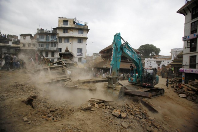 A crane removes debris from the site of a building that collapsed in an earthquake in Kathmandu, Nepal, Saturday, April 25, 2015. A strong magnitude-7.9 earthquake shook Nepal's capital and the densely populated Kathmandu Valley before noon Saturday, causing extensive damage with toppled walls and collapsed buildings, officials said. (AP Photo/ Niranjan Shrestha)