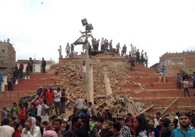 People stand around damage caused by an earthquake at Durbar Square in Kathmandu, Nepal, Saturday, April 25, 2015. A strong magnitude-7.9 earthquake shook Nepal's capital and the densely populated Kathmandu Valley before noon Saturday, causing extensive damage with toppled walls and collapsed buildings, officials said. (AP Photo/ Niranjan Shrestha)