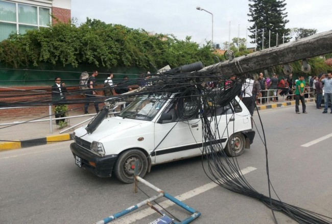 A car stands under the weight of an electric pole after it collapsed following an earthquake in Kathmandu, Nepal, Saturday, April 25, 2015. A strong magnitude-7.9 earthquake shook Nepal's capital and the densely populated Kathmandu Valley before noon Saturday, causing extensive damage with toppled walls and collapsed buildings, officials said. A magnitude-6.6 aftershock hit about an hour later, and smaller aftershocks continued to ripple through the region for hours. (AP Photo/Tashi Sherpa)