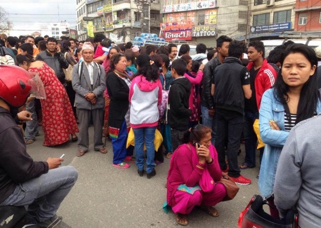 A group of people gather outdoors on a street as an earthquake hits Kathmandu city, Nepal, Saturday, April 25, 2015. A strong magnitude-7.9 earthquake shook Nepal's capital and the densely populated Kathmandu Valley before noon Saturday, causing extensive damage with toppled walls and collapsed buildings, officials said. (AP Photo/ Niranjan Shrestha)