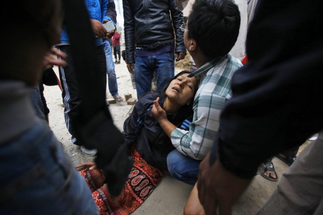 A woman cries as her son remains trapped in the debris of a building that collapsed in an earthquake in Kathmandu, Nepal, Saturday, April 25, 2015. A strong magnitude-7.9 earthquake shook Nepal's capital and the densely populated Kathmandu Valley before noon Saturday, causing extensive damage with toppled walls and collapsed buildings, officials said. (AP Photo/ Niranjan Shrestha)