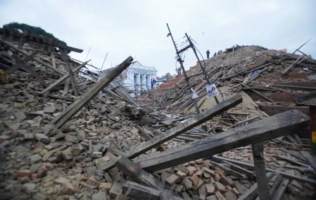 Debris lie at Durbar Square after an earthquake in Kathmandu, Nepal, Saturday, April 25, 2015. A strong magnitude-7.9 earthquake shook Nepal's capital and the densely populated Kathmandu Valley before noon Saturday, causing extensive damage with toppled walls and collapsed buildings, officials said. (AP Photo/ Niranjan Shrestha)