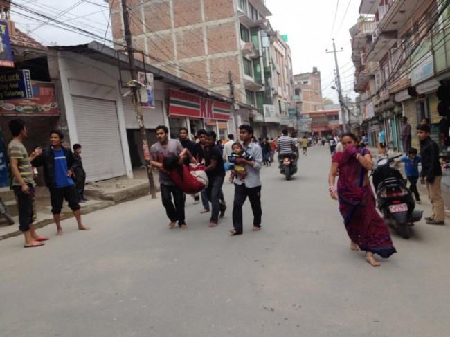 In this photo provided by Guna Raj Luitel, an injured woman is carried just after an earthquake in Kathmandu, Nepal, Saturday, April 25, 2015. A powerful earthquake shook Nepal's capital and the densely populated Kathmandu Valley before noon Saturday, collapsing houses, leveling centuries-old temples and cutting open roads in the worst temblor in the Himalayan nation in over 80 years. (Guna Raj Luitel via AP)