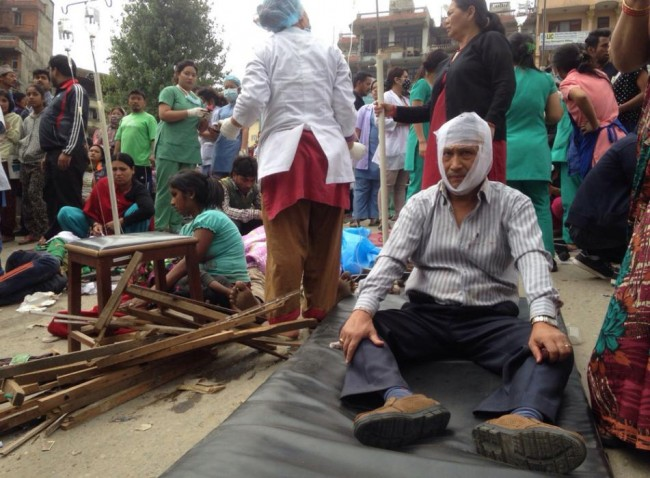 Injured people receive treatment outside the Medicare Hospital in Kathmandu, Nepal, Saturday, April 25, 2015. A strong magnitude-7.9 earthquake shook Nepal's capital and the densely populated Kathmandu Valley before noon Saturday, causing extensive damage with toppled walls and collapsed buildings, officials said. (AP Photo/ Niranjan Shrestha)