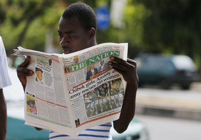 A man is seen reading a newspaper featuring a front page article about a group of women being rescued by the Nigerian army, in Abuja, Nigeria April 29, 2015. More than 200 schoolgirls abducted from their school dormitories by Boko Haram militants last year are not among the nearly 300 girls and women rescued in an army operation on Tuesday, an army spokesman said. Nigeria's army said it had rescued 200 girls and 93 women on Tuesday during a military operation to wrest back the Sambisa Forest in the northeast from the militant group. REUTERS/Afolabi Sotunde