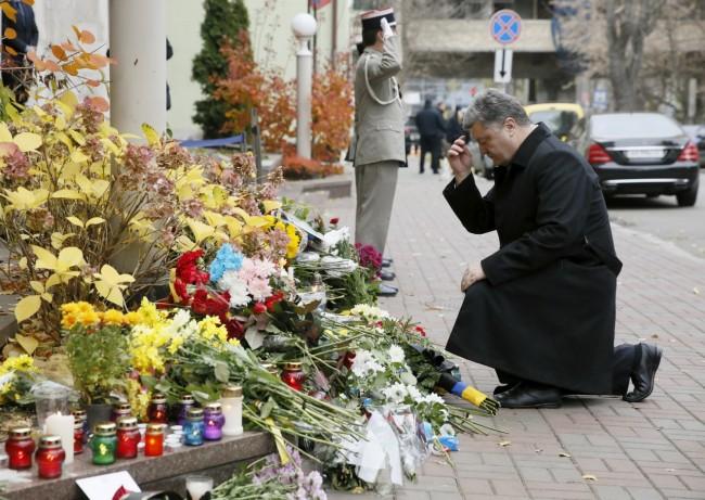 Ukraine's President Petro Poroshenko kneels near the French embassy as he commemorates victims of attacks in Paris, in Kiev, Ukraine, November 14, 2015. REUTERS/Valentyn Ogirenko