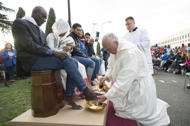 """In this handout picture released by the Vatican Press Office, Pope Francis performs the foot-washing ritual at the Castelnuovo di Porto refugees center near Rome on March 24, 2016. Pope Francis washed the feet of 11 young asylum seekers and a worker at their reception centre to highlight the need for the international community to provide shelter to refugees. Several of the asylum seekers, one holding a baby in her arms, were reduced to tears as the 79-year-old pontiff kneeled before them, pouring water over their feet, drying them with a towel and bending to kiss them. / AFP / STR / RESTRICTED TO EDITORIAL USE - MANDATORY CREDIT """"AFP PHOTO / OSSERVATORE ROMANO"""" - NO MARKETING NO ADVERTISING CAMPAIGNS - DISTRIBUTED AS A SERVICE TO CLIENTS"""