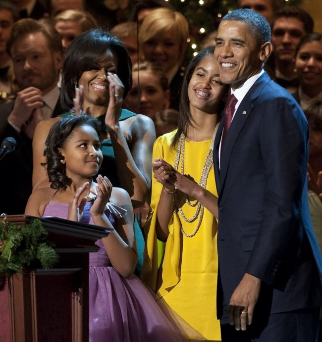 """US President Barack Obama, First Lady Michelle Obama (L) and their daughters, Sasha (2nd L) and Malia (2nd R), after Obama spoke during the taping of """"Christmas in Washington,"""" at the National Building Museum in Washington, DC, December 11, 2011. The show, hosted by Conan O'Brien, features performances and appearances by Justin Bieber, Cee Lo Green, Jennifer Hudson, Victoria Justice and The Band Perry and airs on television December 16. AFP PHOTO / Saul LOEB (Photo credit should read SAUL LOEB/AFP/Getty Images)"""