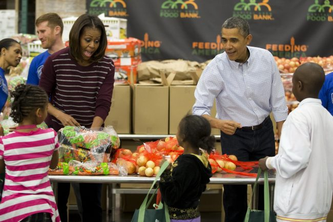 President Barack Obama, right, and first lady Michelle Obama participate in a Thanksgiving service project by handing out food at the Capital Area Food Bank on Wednesday, Nov. 27, 2013 in Washington. The Capital Area Food Bank distributes 30 million pounds of food annually. (AP Photo/ Evan Vucci)