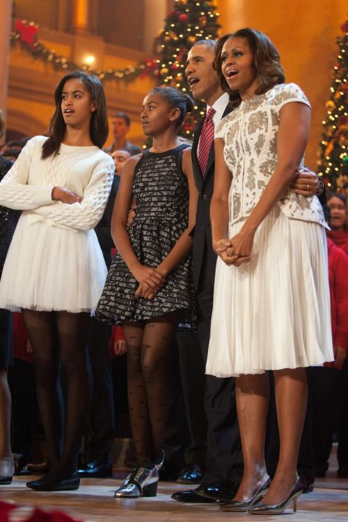 """WASHINGTON, DC - DECEMBER 15:  U.S. President Barack Obama and first lady Michelle Obama, along with daughters Malia (left) and Sasha, sing during the finale of TNT's  """"Christmas in Washington"""" on December 15, 2013 in Washington, DC.  The program benefits the Children's National Health System.  (Photo by Martin H. Simon-Pool/Getty Images)"""