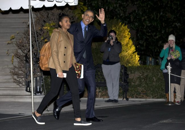 President Barack Obama waves as he and his daughter Sasha walk from the White House to board Marine One, Friday, Dec. 18, 2015, in Washington, for the short trip to Andrews Air Force Base en route to San Bernardino, Calif. (AP Photo/Carolyn Kaster)