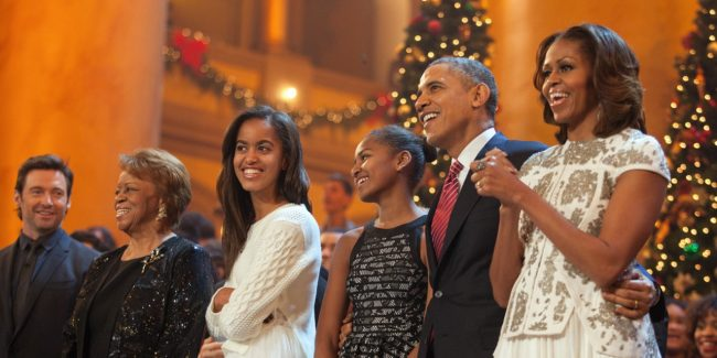"""WASHINGTON, DC - DECEMBER 15:  U.S. President Barack Obama and first lady Michelle Obama, along with daughters Malia (left) and Sasha, sing during the finale of TNT's """"Christmas in Washington"""" on December 15, 2013 in Washington, DC.  The program benefits the Children's National Health System. Also shown are the president's mother-in-law, Marian Robinson, and the program's host, actor Hugh Jackman. (Photo by Martin H. Simon-Pool/Getty Images)"""