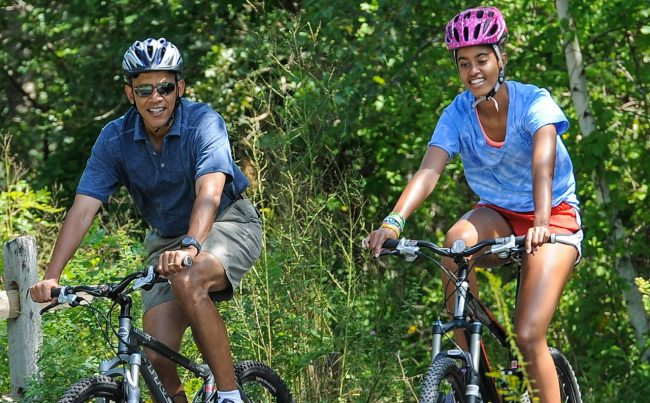 WEST TISBURY , MA - AUGUST 16: U.S. President Barack Obama (L) his daughter Malia Obama ride a bike during a vacation on Martha's Vineyard August 16, 2013in West Tisbury, Massachusetts. Obama and his family are on a weeklong vacation.  (Photo by Rick Friedman-Pool/Getty Images)