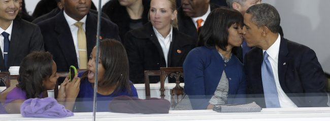 FOR USE AS DESIRED, YEAR END PHOTOS - FILE - President Barack Obama kisses first lady Michelle Obama as their daughters Sasha, left, and Malia, second from left, look on during the Inaugural parade, Monday, Jan. 21, 2013, in Washington. Thousands  marched during the 57th Presidential Inauguration parade after the ceremonial swearing-in of President Barack Obama. (AP Photo/Gerald Herbert, File)