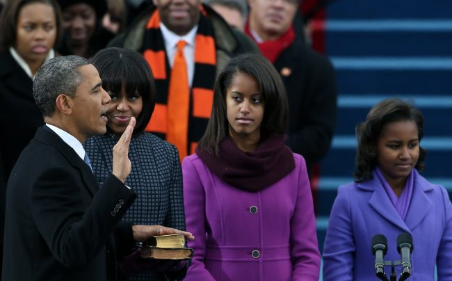 WASHINGTON, DC - JANUARY 21:  U.S. President Barack Obama (L) is sworn inas First lady Michelle Obama and daughters, Sasha Obama (R) and Malia Obama look on during the public ceremonial inauguration on the West Front of the U.S. Capitol January 21, 2013 in Washington, DC.   Barack Obama was re-elected for a second term as President of the United States.  (Photo by Justin Sullivan/Getty Images)